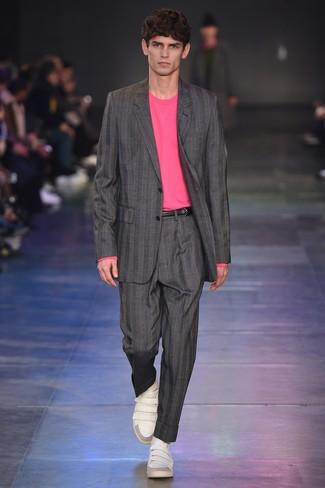 Модный лук: серый костюм в вертикальную полоску, ярко-розовый свитер с круглым вырезом, белые кожаные низкие кеды, черный кожаный ремень