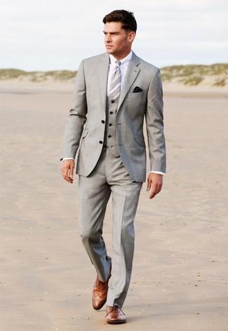 Как и с чем носить: серый костюм-тройка, белая классическая рубашка, коричневые кожаные броги, серый галстук в вертикальную полоску