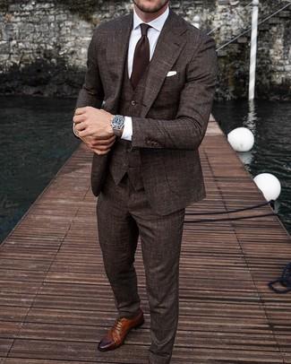 Как и с чем носить: темно-коричневый костюм-тройка, белая классическая рубашка, коричневые кожаные броги, темно-коричневый галстук
