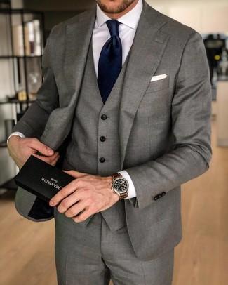 Как и с чем носить: серый костюм-тройка, белая классическая рубашка, темно-синий шелковый галстук, белый нагрудный платок