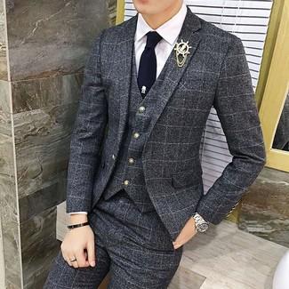 Как и с чем носить: темно-серый костюм-тройка в клетку, белая классическая рубашка, темно-синий галстук, золотая мужская брошь