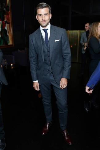 Как и с чем носить: темно-серый шерстяной костюм-тройка, белая классическая рубашка, темно-коричневые кожаные оксфорды, темно-синий вязаный галстук