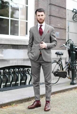 Темно-красный галстук: с чем носить и как сочетать мужчине: Несмотря на то, что это довольно консервативный лук, тандем серого костюма-тройки и темно-красного галстука неизменно нравится стильным молодым людям, неизбежно пленяя при этом сердца прекрасных дам. Чтобы образ не получился слишком вычурным, можно надеть коричневые кожаные туфли дерби.