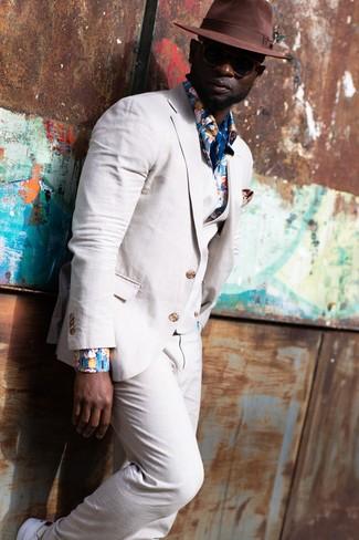 Как и с чем носить: бежевый льняной костюм-тройка, синяя рубашка с длинным рукавом с цветочным принтом, белые низкие кеды, коричневая шерстяная шляпа
