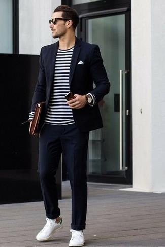 Коричневый кожаный мужской клатч: с чем носить и как сочетать мужчине: Если превыше всего ты ценишь удобство и практичность, обрати внимание на тандем темно-синего костюма и коричневого кожаного мужского клатча. В тандеме с этим луком наиболее выгодно будут смотреться белые кожаные низкие кеды.