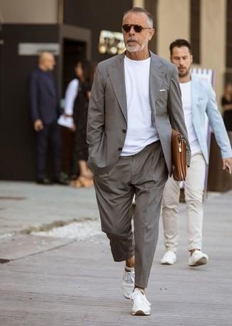 Как одеваться мужчине за 50: Серый костюм и белая футболка с круглым вырезом — ансамбль, который будет неизменно притягивать женские взоры. Такой образ несложно приспособить к повседневным делам, если закончить его белыми кроссовками.