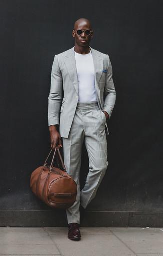 """Коричневая кожаная дорожная сумка: с чем носить и как сочетать мужчине: Дуэт серого костюма в клетку и коричневой кожаной дорожной сумки в мужском образе позволит добиться ощущения """"элегантной свободы"""". Хочешь добавить сюда нотку утонченности? Тогда в качестве обуви к этому ансамблю, стоит выбрать темно-красные кожаные монки с двумя ремешками."""