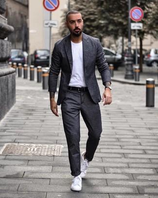 Как и с чем носить: темно-серый шерстяной костюм, белая футболка с круглым вырезом, белые низкие кеды, черный кожаный ремень