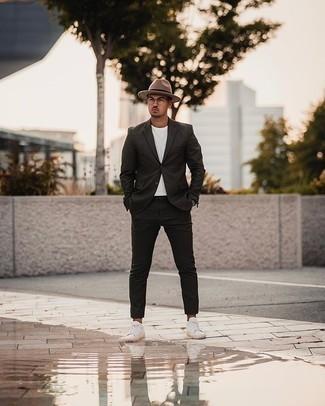 С чем носить прозрачные солнцезащитные очки мужчине: Черный костюм выглядит стильно в сочетании с прозрачными солнцезащитными очками. Пара белых низких кед из плотной ткани очень просто вписывается в этот лук.