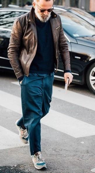 Как и с чем носить: коричневая кожаная косуха, черный свитер с круглым вырезом, темно-синие брюки чинос, бежевые замшевые кроссовки