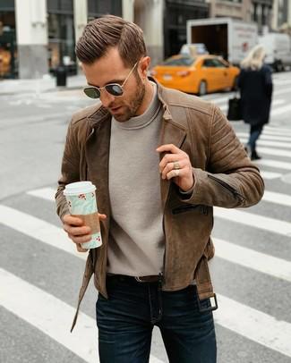 Как и с чем носить: коричневая кожаная косуха, серый свитер с круглым вырезом, темно-синие джинсы, темно-коричневый кожаный ремень
