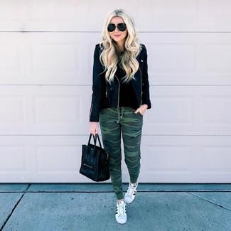 Как и с чем носить: черная кожаная косуха, черный свитер с круглым вырезом, темно-зеленые спортивные штаны с камуфляжным принтом, бело-черные кожаные низкие кеды