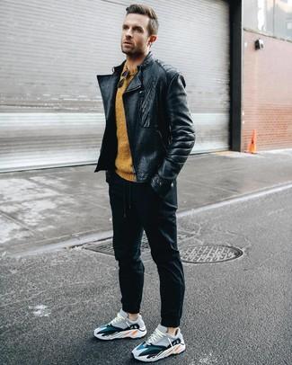 Модный лук: черная кожаная косуха, горчичный свитер с круглым вырезом, черные спортивные штаны, разноцветные кроссовки