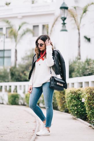 Как и с чем носить: черная кожаная стеганая косуха, белый вязаный свободный свитер, синие джинсы скинни, белые низкие кеды