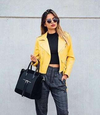 Как и с чем носить: желтая кожаная косуха, черный укороченный топ, темно-серые брюки-галифе в клетку, черная замшевая большая сумка