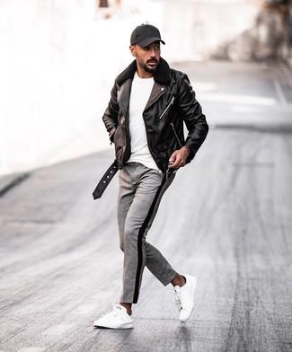Как и с чем носить: черная кожаная косуха, белая футболка с круглым вырезом, серые брюки чинос в шотландскую клетку, белые кожаные низкие кеды