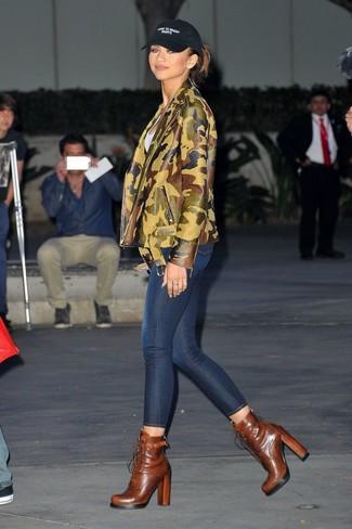 Как и с чем носить: оливковая кожаная косуха с камуфляжным принтом, белая футболка с круглым вырезом, темно-синие джинсы скинни, коричневые кожаные ботильоны на шнуровке
