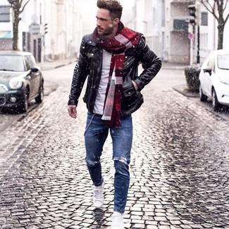 Черная кожаная косуха и синие рваные зауженные джинсы — идеальный выбор, если ты хочешь создать непринужденный, но в то же время стильный образ. Очень стильно здесь будут смотреться белые низкие кеды.