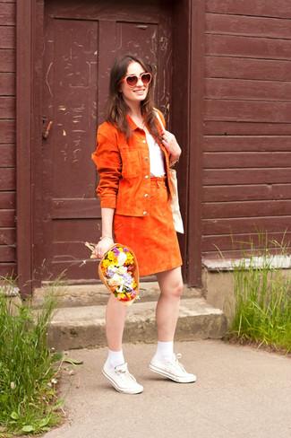 Как и с чем носить: оранжевая замшевая косуха, белая футболка с круглым вырезом, оранжевая замшевая юбка-трапеция, белые низкие кеды из плотной ткани