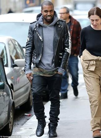 Как Kanye West носит Черная кожаная косуха с принтом, Серый худи, Оливковая футболка с круглым вырезом с камуфляжным принтом, Черные джинсы