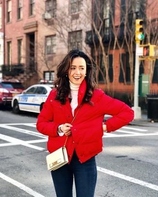 Как и с чем носить: красная куртка-пуховик, белая водолазка, темно-синие джинсы скинни, бежевая кожаная сумка через плечо