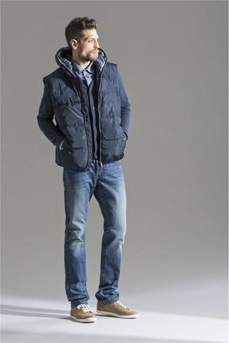 Темно-серая стеганая куртка без рукавов: с чем носить и как сочетать мужчине: Темно-серая стеганая куртка без рукавов и синие джинсы — хороший образ для похода в кино или марафона по городским барам. Вкупе с этим луком удачно выглядят светло-коричневые низкие кеды.