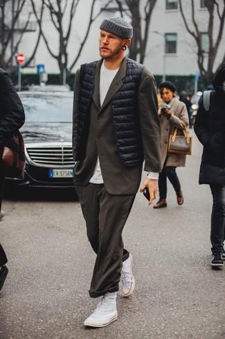 Серая шапка: с чем носить и как сочетать мужчине: Такое лаконичное и удобное сочетание вещей, как черная куртка без рукавов и серая шапка, придется по душе молодым людям, которые любят проводить дни активно. Хочешь сделать лук немного строже? Тогда в качестве обуви к этому образу, обрати внимание на белые высокие кеды из плотной ткани.