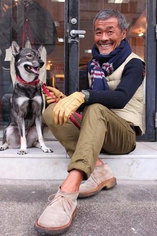 Как и с чем носить: бежевая стеганая куртка без рукавов, темно-синий свитер с круглым вырезом, оливковые брюки чинос, бежевые замшевые ботинки дезерты