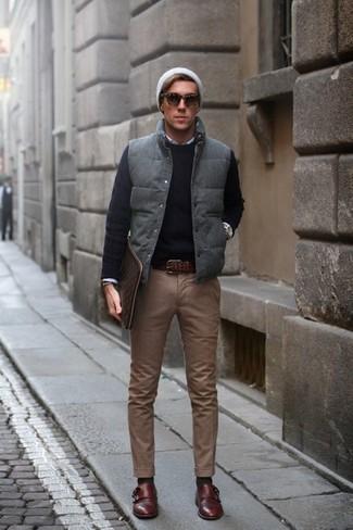 Как и с чем носить: серая стеганая куртка без рукавов, черный свитер с круглым вырезом, белая рубашка с длинным рукавом, коричневые брюки чинос