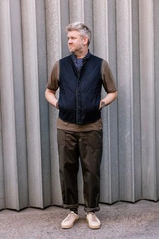 Темно-синяя куртка без рукавов: с чем носить и как сочетать мужчине: Современным парням, которые предпочитают быть в курсе последних тенденций, рекомендуем обратить внимание на это сочетание темно-синей куртки без рукавов и темно-коричневых брюк чинос. Чтобы добавить в ансамбль толику небрежности , на ноги можно надеть бежевые низкие кеды из плотной ткани.