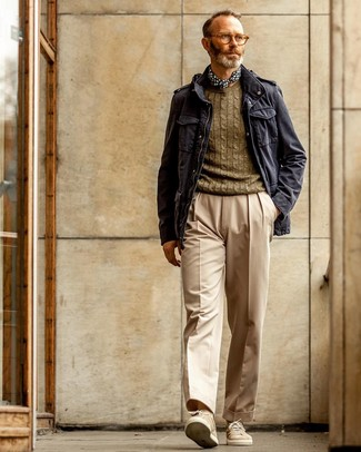 Как и с чем носить: темно-синяя куртка в стиле милитари, оливковый вязаный свитер, бежевые классические брюки, бежевые замшевые низкие кеды