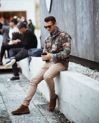 Как и с чем носить: оливковая куртка в стиле милитари с камуфляжным принтом, синяя джинсовая рубашка, бежевые зауженные джинсы, коричневые замшевые классические ботинки