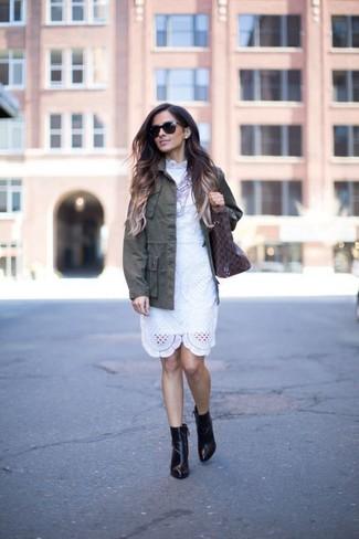 Как и с чем носить: оливковая куртка в стиле милитари, белое кружевное платье-футляр, черные кожаные ботильоны, темно-коричневая кожаная большая сумка с принтом