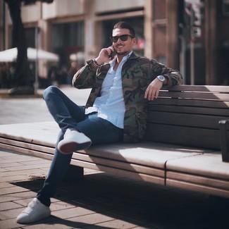 Как и с чем носить: оливковая куртка в стиле милитари с камуфляжным принтом, голубая рубашка с длинным рукавом с принтом, темно-синие брюки чинос, белые низкие кеды