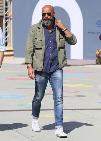 Как и с чем носить: оливковая куртка в стиле милитари, темно-синяя рубашка с длинным рукавом, синие джинсы, белые высокие кеды