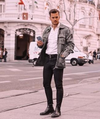 Как и с чем носить: оливковая куртка в стиле милитари, белая рубашка с длинным рукавом, черные зауженные джинсы, черные кожаные ботинки челси