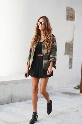 Как и с чем носить: оливковая куртка в стиле милитари с камуфляжным принтом, черный укороченный топ, черная короткая юбка-солнце, черные кожаные ботильоны