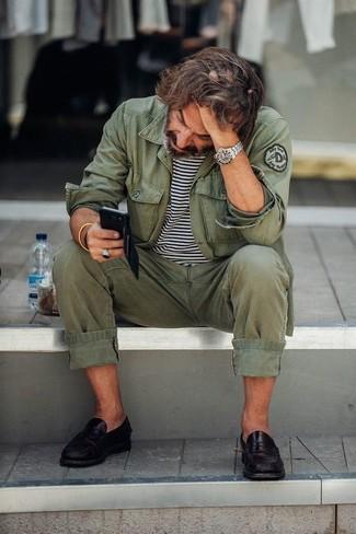 Как и с чем носить: оливковая куртка в стиле милитари, бело-черная футболка с круглым вырезом в горизонтальную полоску, оливковые брюки чинос, черные кожаные лоферы