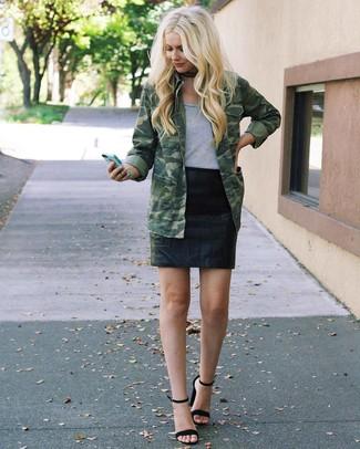 Как и с чем носить: оливковая куртка в стиле милитари с камуфляжным принтом, серая футболка с круглым вырезом, черная кожаная мини-юбка, черные замшевые босоножки на каблуке