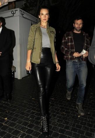 Как и с чем носить: оливковая куртка в стиле милитари, бело-черная футболка с круглым вырезом в горизонтальную полоску, черные кожаные узкие брюки, черные кожаные ботильоны на шнуровке