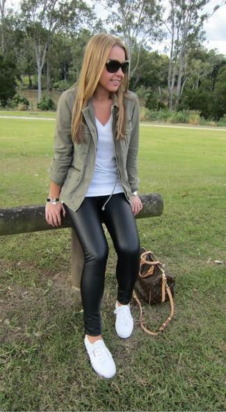 Как и с чем носить: оливковая куртка в стиле милитари, белая футболка с v-образным вырезом, черные кожаные леггинсы, белые низкие кеды