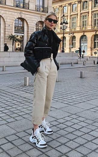 Как и с чем носить: черная куртка-пуховик, черная водолазка, бежевые брюки-галифе, бело-черные кроссовки