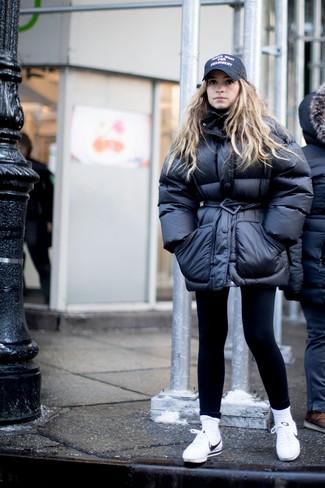 Как и с чем носить: черная куртка-пуховик, черные леггинсы, белые кожаные низкие кеды, черная кепка с принтом