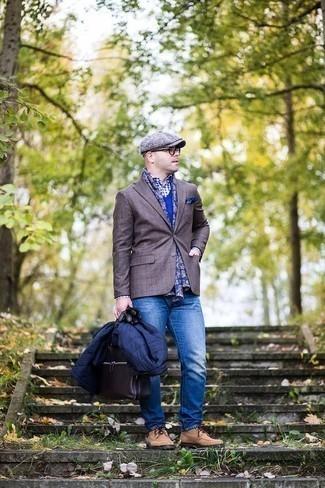 Модные мужские луки 2020 фото в прохладную погоду: Сочетание темно-синей легкой куртки-пуховика и синих джинсов позволит подчеркнуть твою индивидуальность и выгодно выделиться из толпы. И почему бы не добавить в повседневный образ толику изысканности с помощью светло-коричневых замшевых туфель дерби?