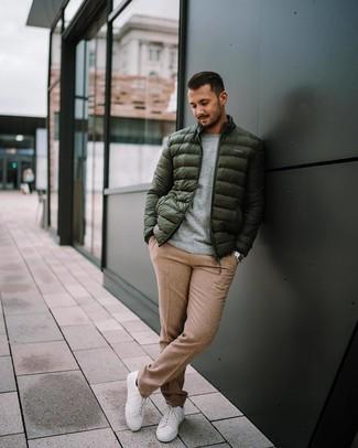 Как и с чем носить: темно-зеленая куртка-пуховик, серый свитер с круглым вырезом, светло-коричневые шерстяные классические брюки, белые низкие кеды
