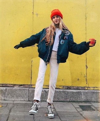 Как и с чем носить: темно-бирюзовая куртка-пуховик, серый укороченный топ с принтом, бежевые джинсы, черно-белые высокие кеды из плотной ткани