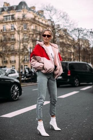 Как и с чем носить: розовая куртка-пуховик, бело-черная футболка с круглым вырезом с принтом, серые джинсы, белые ботильоны на резинке