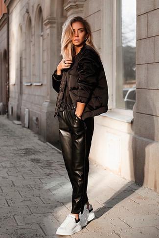 Как и с чем носить: черная куртка-пуховик, черная футболка с круглым вырезом, черные кожаные пижамные штаны, белые кожаные низкие кеды