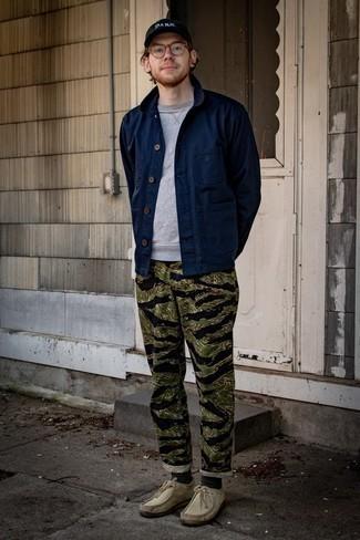 Мужские луки: Темно-синяя куртка-рубашка смотрится великолепно в тандеме с оливковыми брюками чинос с камуфляжным принтом. В паре с этим луком органично выглядят бежевые замшевые ботинки дезерты.