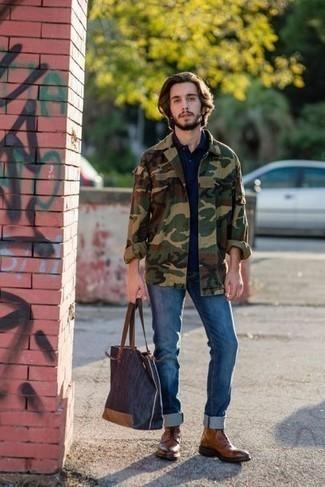 Темно-синяя большая сумка из плотной ткани: с чем носить и как сочетать мужчине: Оливковая куртка-рубашка с камуфляжным принтом и темно-синяя большая сумка из плотной ткани — отличная формула для создания приятного и практичного ансамбля. Любишь яркие идеи? Закончи лук коричневыми кожаными повседневными ботинками.